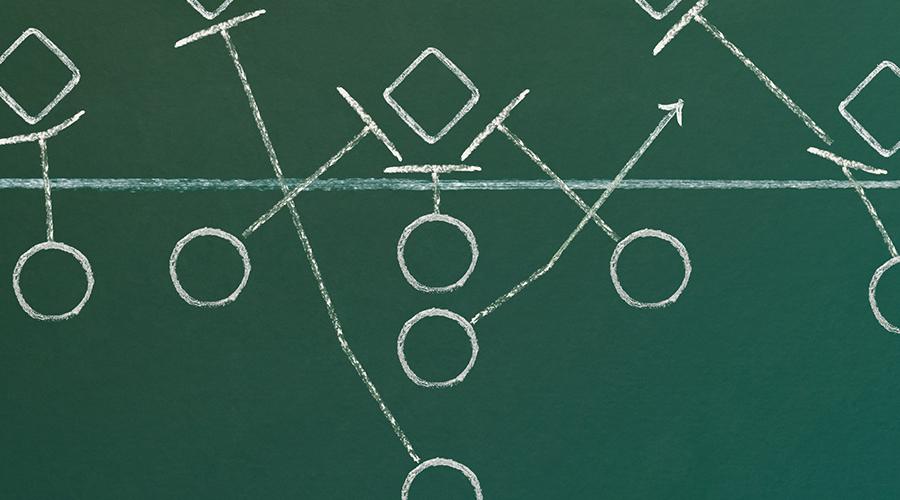 An American football play diagram on a green chalkboard